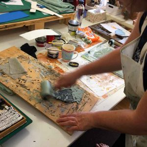 Kim Herringe inking up a reductive lino print